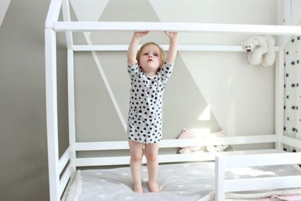 Une petite fille qui se tient sur l'armature d'un lit cabane au sol
