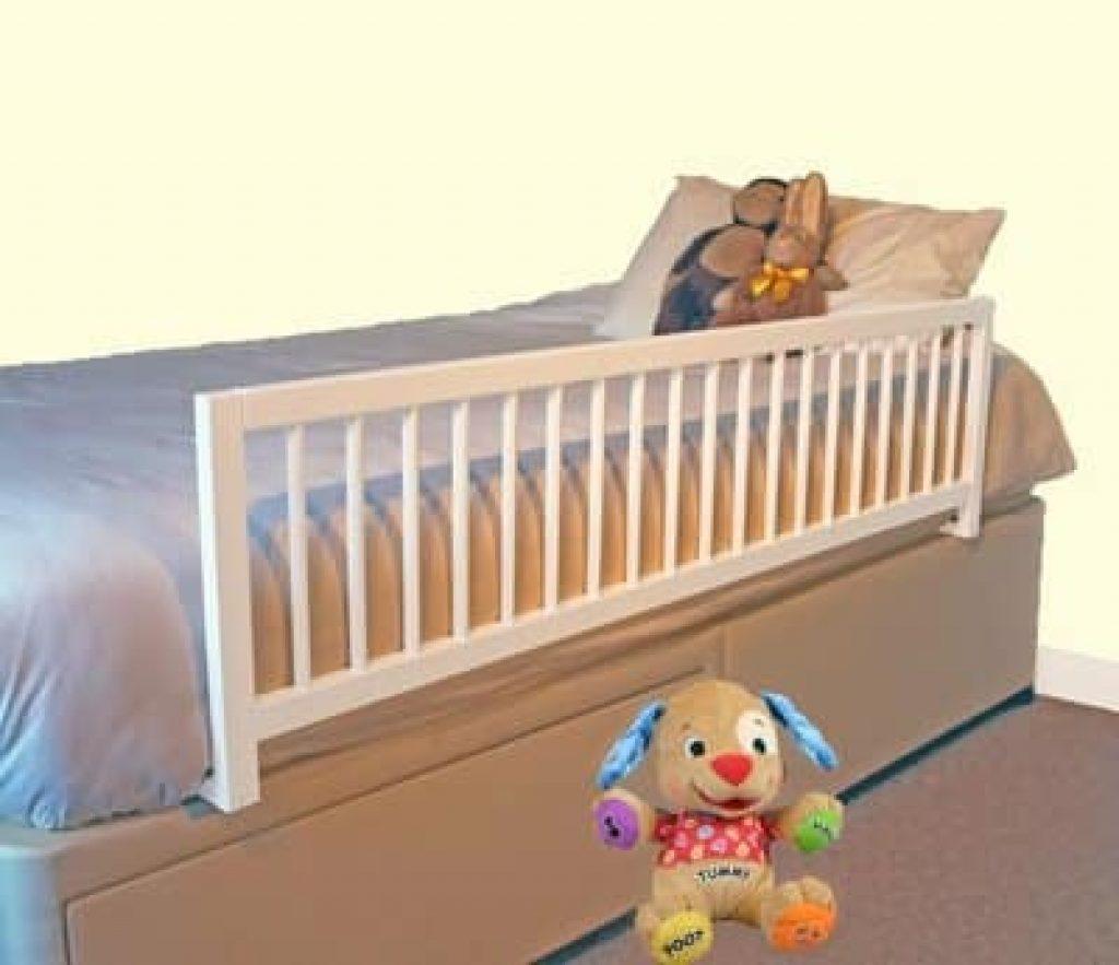 Une barrière de lit en bois blanc placée sur un lit